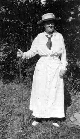 Photo of Cather standing, holding a walking stick.