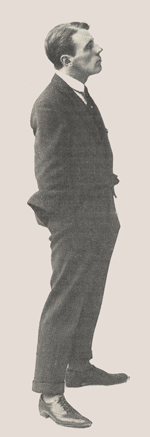 Profile of a young man standing with his hands in his pockets.