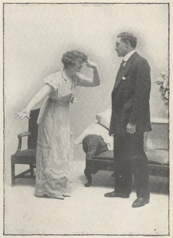 Miss Billie Burke as Lily stands in front of Mr. Herbert as Captain Jeyes with one arm outstretched and the index finger of the other arm pointing to her temple.