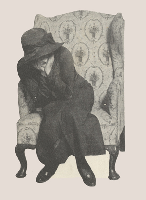 A woman sitting in a chair with her face in her hands.