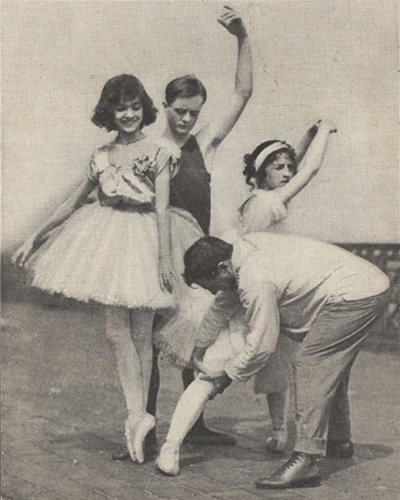 A male ballet instructor working with one of his pupils while several others look on.