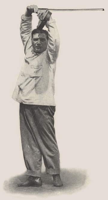Male ballet instructor holding violin and bow over his head.
