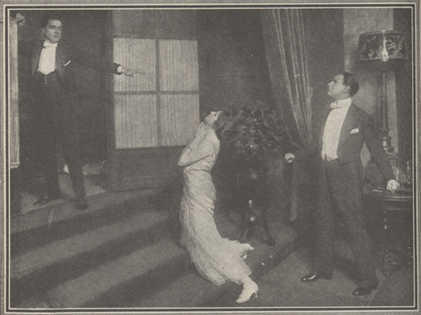 Photograph of an actress kneeling on somes steps in front of an actor with another actor standing behind her.