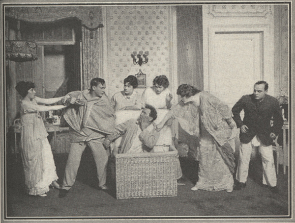 Photograph of several actors and actresses gather around an actor who is emerging from hiding in a wicker basket.