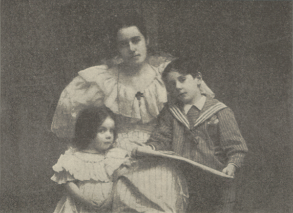 Studio portrait of Mrs. Nevin seated with her daughter Doris leaning against her on her right and her son Paul leaning against her on her left holding a large piece of paper in his hands