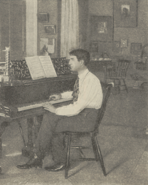 Ethelbert Nevin seated on a cane-back chair at a piano, looking at the music with his hands on the keys of the piano