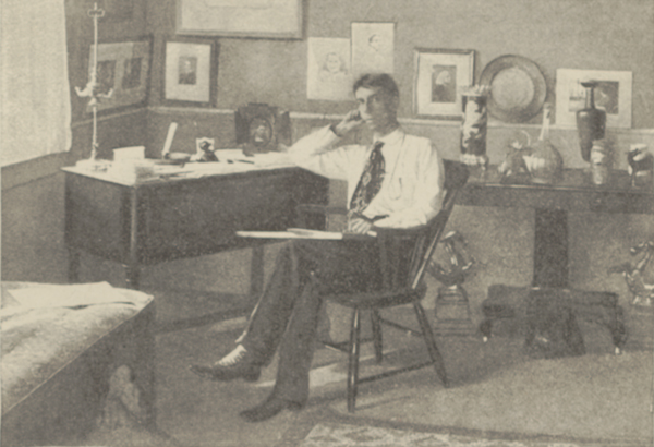 Ethelbert Nevin seated in his studio in a cane-back chair in front of a desk, resting his elbow on the desk and holding papers in his lap