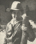 Photograph of Willa Cather wearing a western-style hat and holding a large stick of wood.